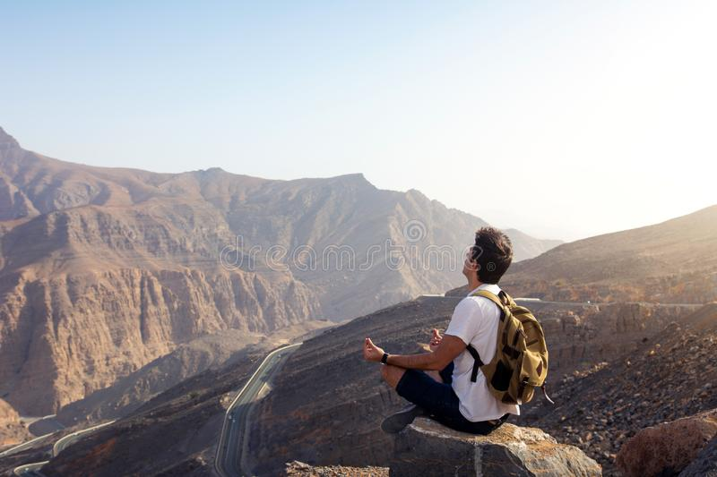 Man meditating on the mountain top stock photo