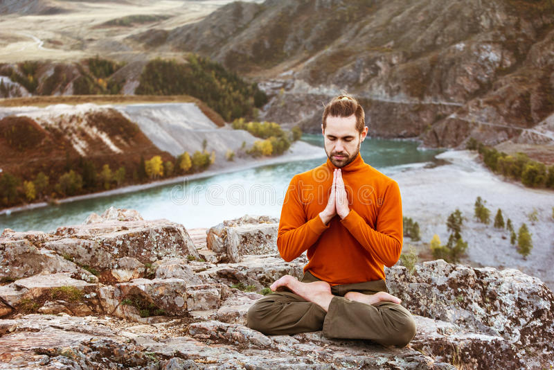 Man meditating in the mountains. Man meditating on the Altay mountains background stock image