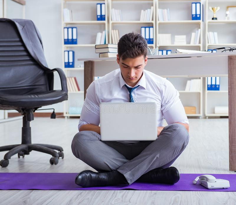Man meditating in the office to cope with stress. The man meditating in the office to cope with stress stock photo