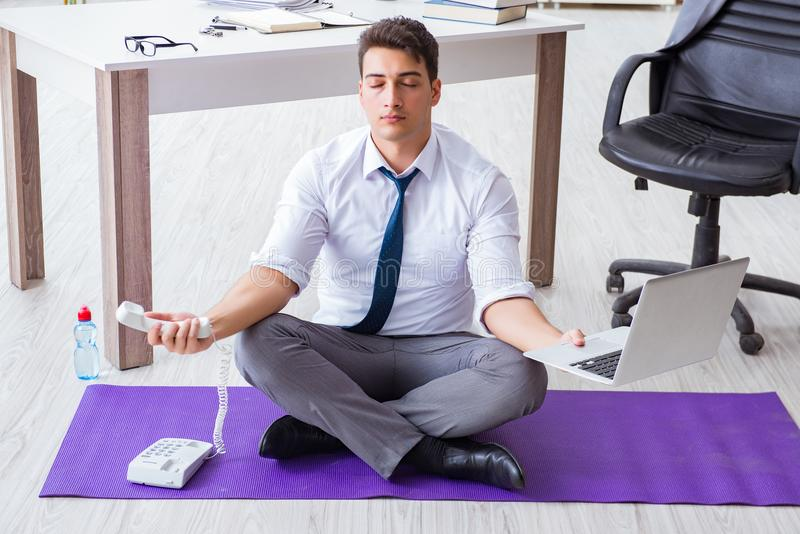 The man meditating in the office to cope with stress. Man meditating in the office to cope with stress royalty free stock images