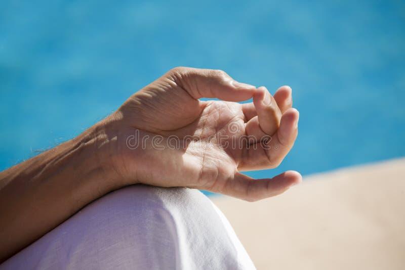 Man meditating at the pool. Man meditating at the swimming pool side royalty free stock images