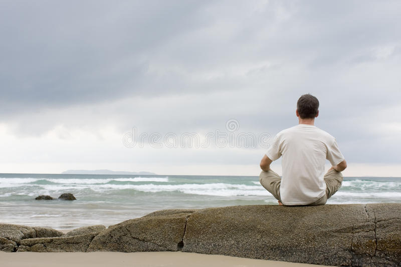 Man meditating on a rock at the sea. In the morning stock image