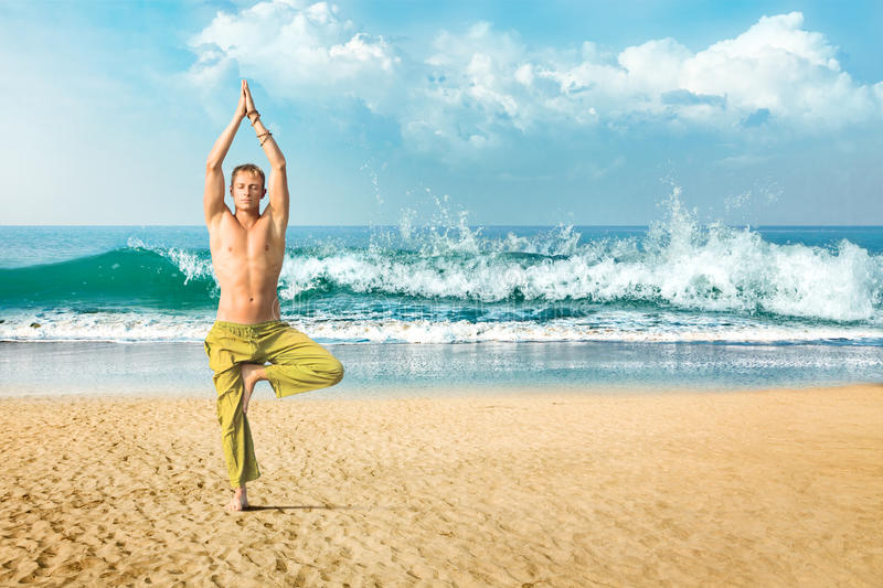 Man meditating in tree position. Young man doing yoga and meditating in tree position at sea beach stock photos