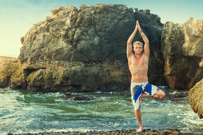 Man meditating in tree position. Young man doing yoga and meditating in tree position at sea beach royalty free stock images