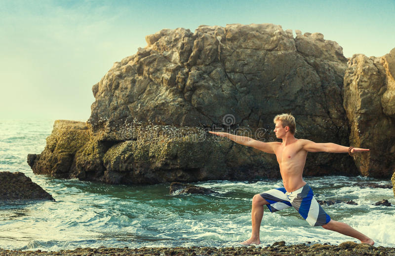 Man meditating in warrior pose. Young man doing yoga and meditating in warrior pose at sea beach stock photography