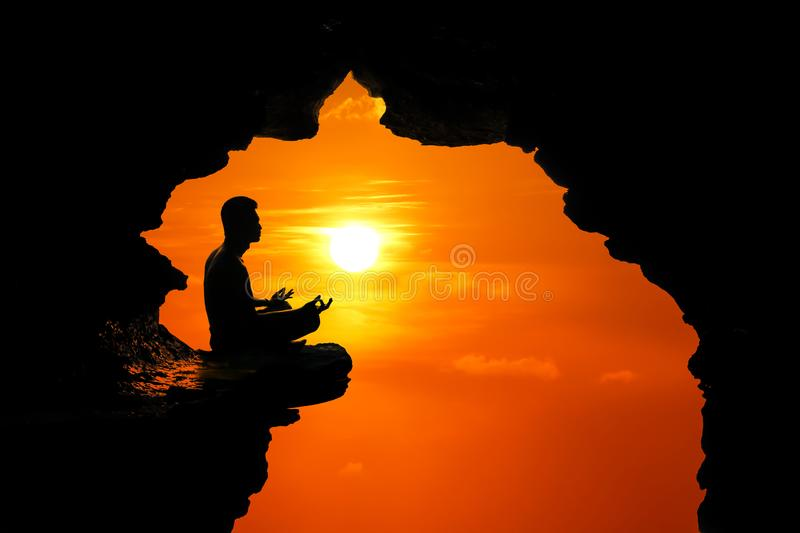 Man meditation and praying in the cave on the high cliff at sunset red sky. Background royalty free stock image