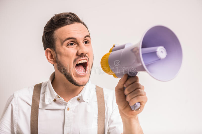 Man with megaphone. Young man is shouting in a megaphone over grey background royalty free stock photography