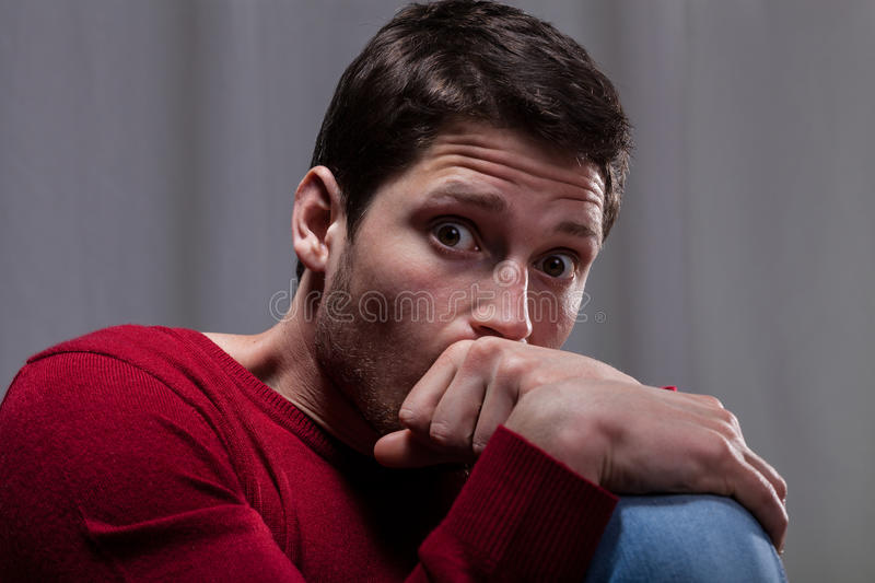 Man with mental disease. Young man with mental disease sitting curled up and scared stock images