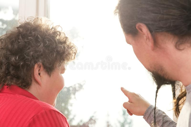 Man and mentally disabled woman looking out of the window. A men and a mentally disabled women looking out of the window royalty free stock photos