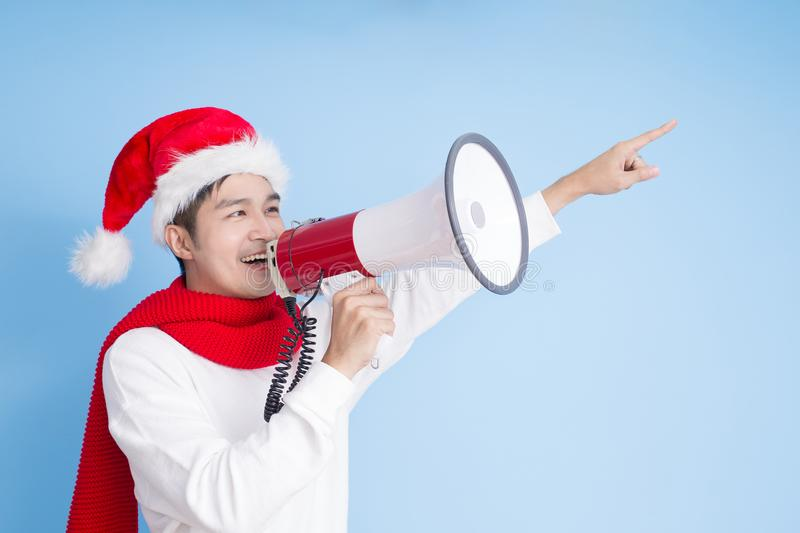 Man with merry christmas. Man take microphone and show something with merry christmas on the blue background royalty free stock images