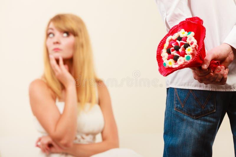 Man met de bloemen van de suikergoedbos en ongelukkige vrouw royalty-vrije stock afbeelding