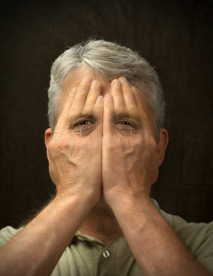 Man met een bipolaire stoornis die probeert zijn gevoelens te verbergen, maar zijn traan gevulde ogen laten zien door zijn handen stock foto's