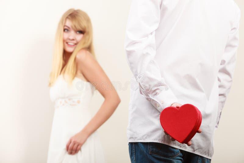 Man met hart gevormde giftdoos voor vrouw stock afbeeldingen