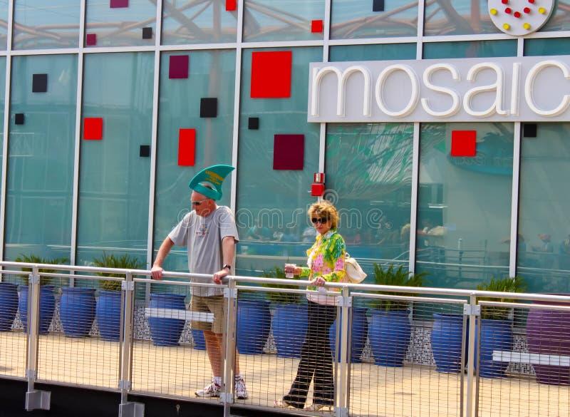 Man met Landshark-hoed en vrouw die met drank op balkon neer met bezinning van mensen die P bekijken partying stock foto's