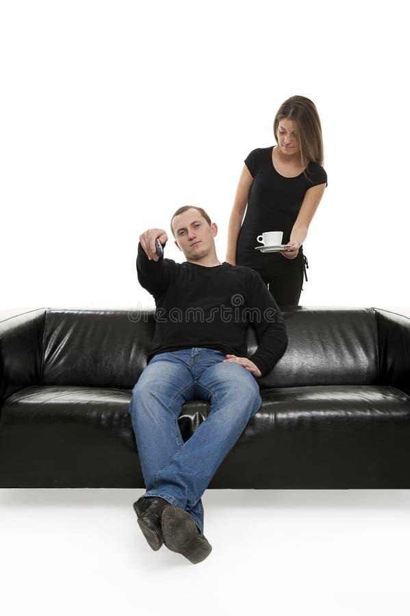 Man met TVafstandsbediening en vrouw naast stock afbeelding