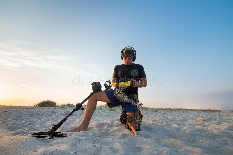 Man with a metal detector on a sea sandy beach stock photos