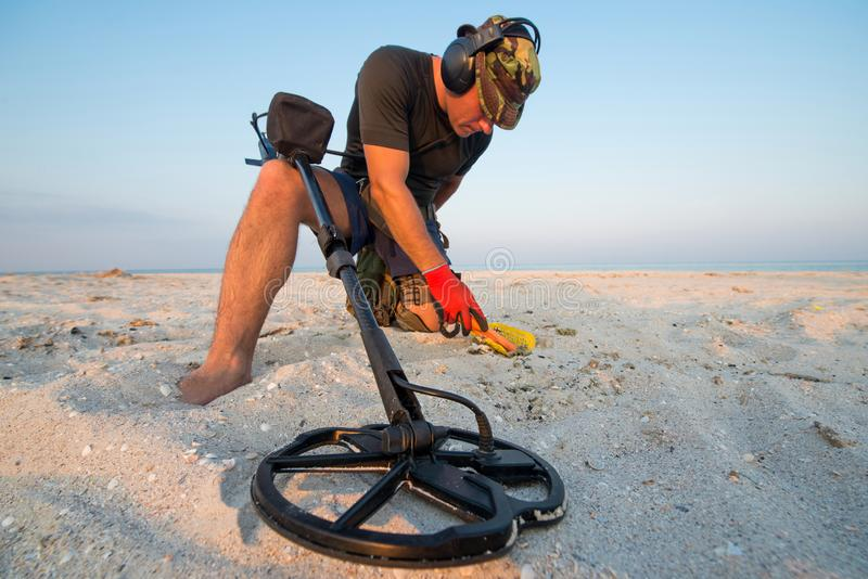 Man with a metal detector on a sea sandy beach royalty free stock images