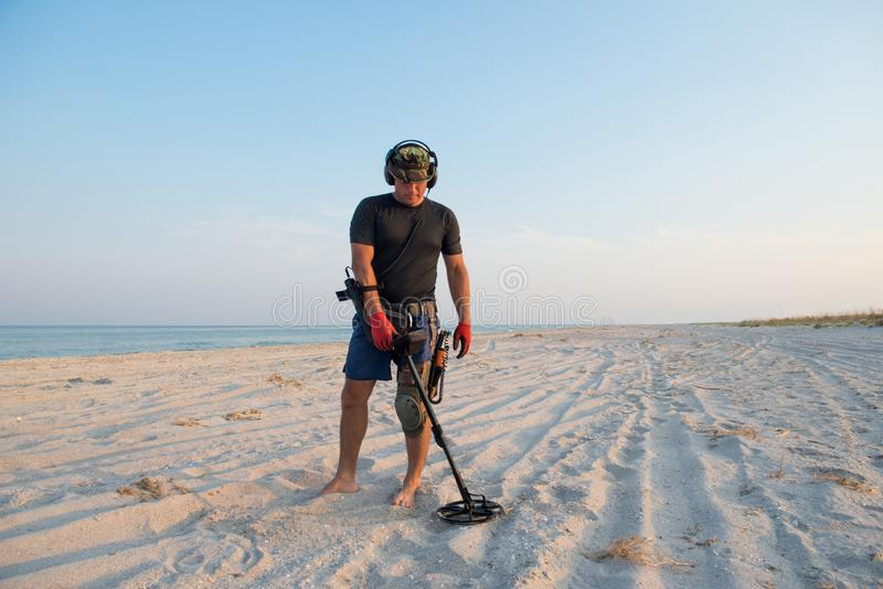 Man with a metal detector on a sea sandy beach royalty free stock photos