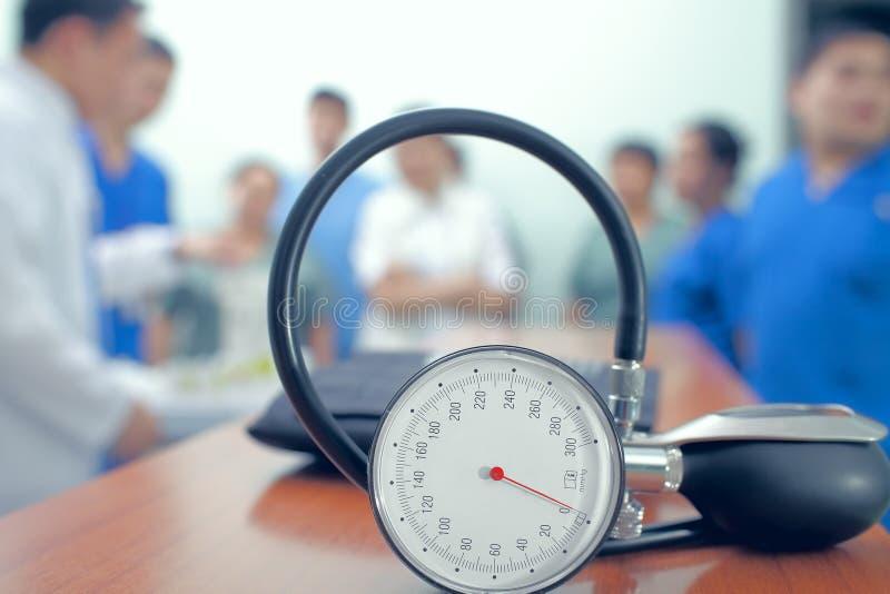 Manômetro na tabela no fundo do grupo de doutores fotografia de stock