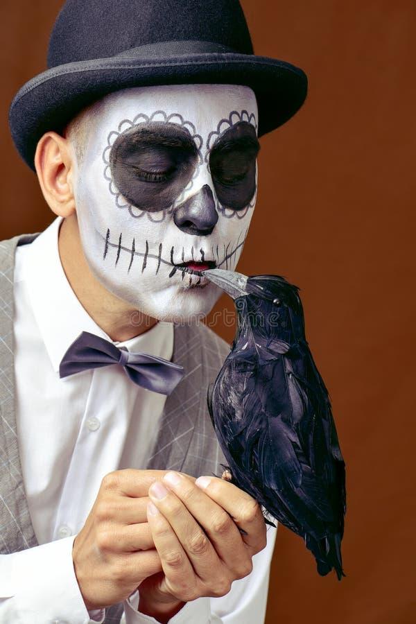 Man with mexican calaveras makeup kissing a black crow stock photos