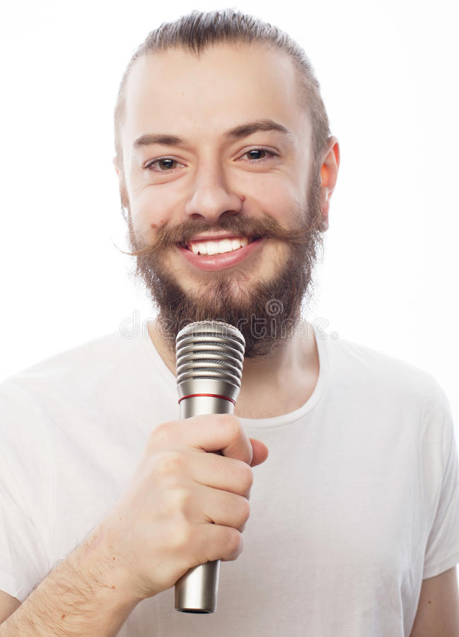 Man with microphone. Life style concept: a young man with a beard wearing a white shirt holding a microphone and singing.Isolated on white stock photos