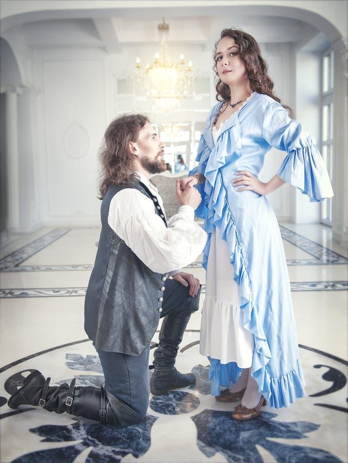 Man in middeleeuws kostuum die zich op de knie vóór vrouw bevinden stock foto