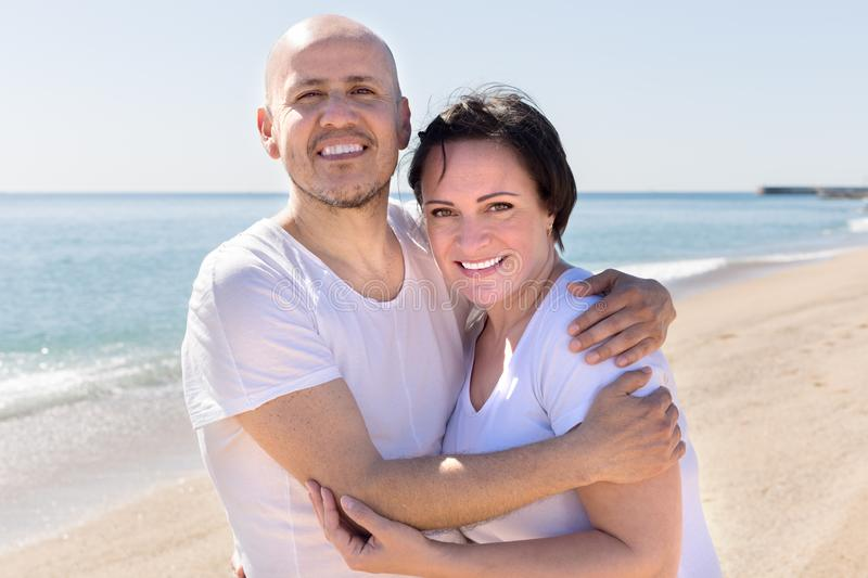 Man and a middle-aged woman in white T-shirt on the beach. Smiling men and a middle-aged women in white T-shirt on the beach stock image