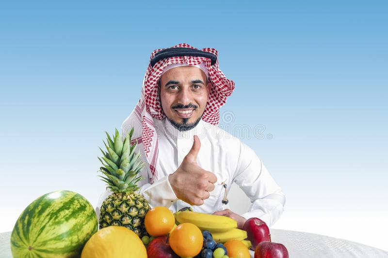 Man from the Middle East in a traditional Arab national costume, stands in front of a mountain of fresh fruit, joyfully smiles and. Holds his finger up stock photography