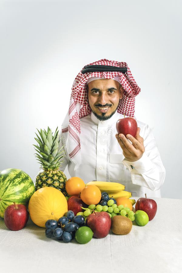 Man from the Middle East in a traditional Arab national costume, stands in front of a mountain of fresh fruit, smiles joyfully and. Holds a red apple in his royalty free stock image