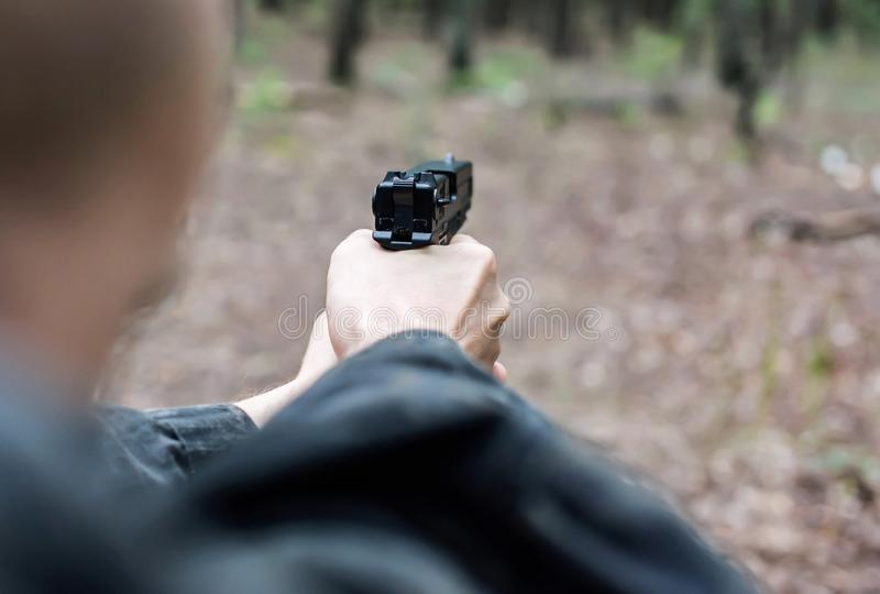 A man in military clothing is aiming with a pistol. In the forest stock image