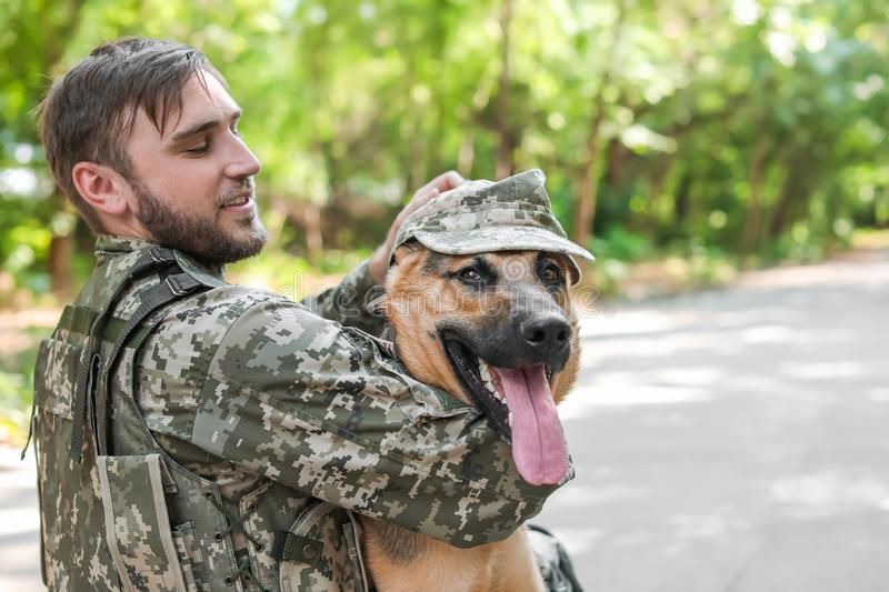Man in military uniform with German shepherd dog. Outdoors royalty free stock photography