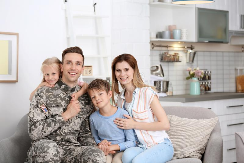 Man in military uniform with his family on sofa royalty free stock photos