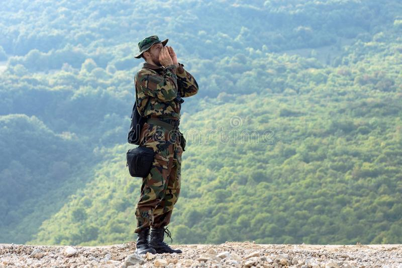 Shouting in nature. The man in military uniform is shouting in the nature on green background stock photography