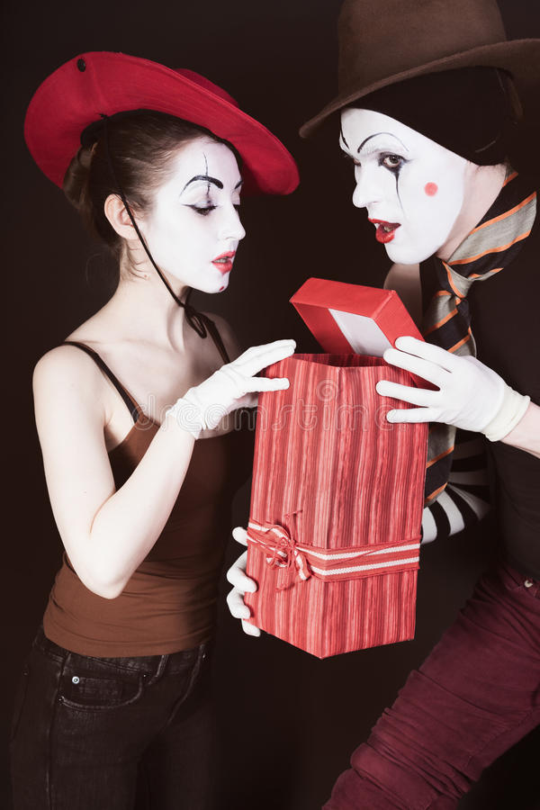 A man mime gives a gift to a woman stock photography