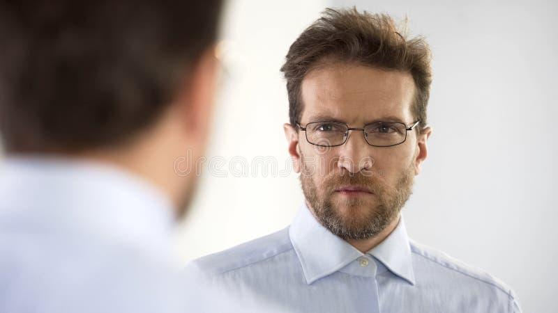 Man missbelåtet med hans exponeringsglas och att tänka om visionkorrigeringstillvägagångssätt royaltyfria foton