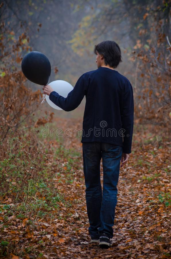 Man in misty autumn forest goes and looks at black and white balloon in hand, thinks about life, good and evil, choice stock photography