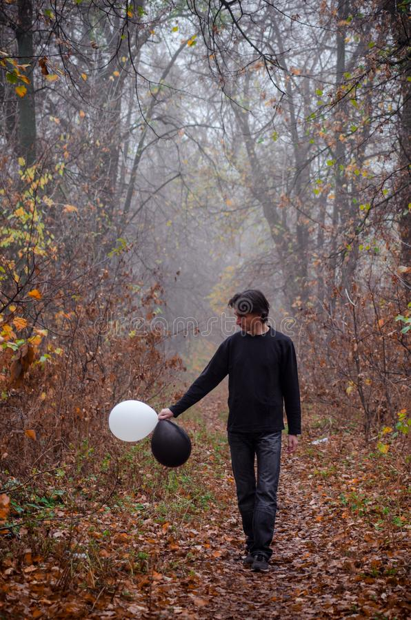 Man in misty autumn forest goes and looks at a black and white balloon, thinks about life, good and evil, makes a choice stock images