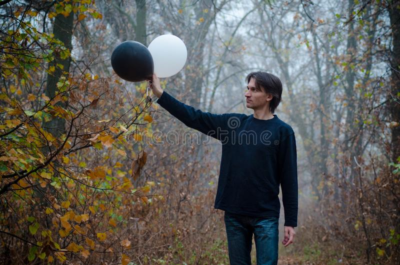 Man in misty autumn forest looks at black and white balloon in his hand, concept of good and evil, makes choice, closeup stock photography