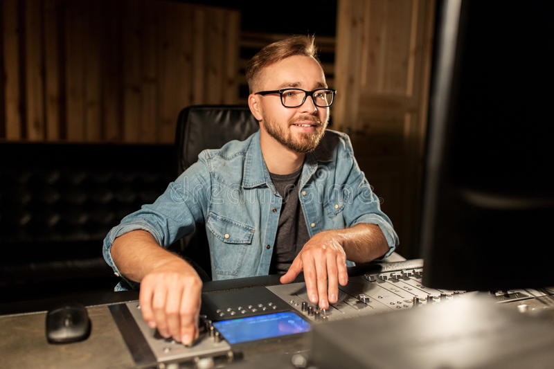 Man at mixing console in music recording studio stock images