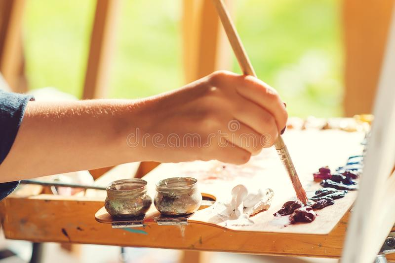 Man mixing paints with paintbrush on palette, close up. Artist`s palette. Artist painting still life outdoors at nature. Art, creativity and hobby royalty free stock image