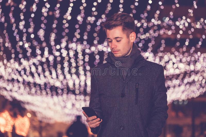 Man with mobile phone on the street with Christmas decoration royalty free stock photo