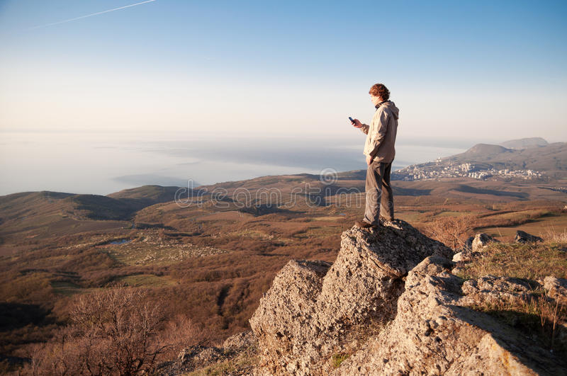 Man with mobile phone on the top of world stock image