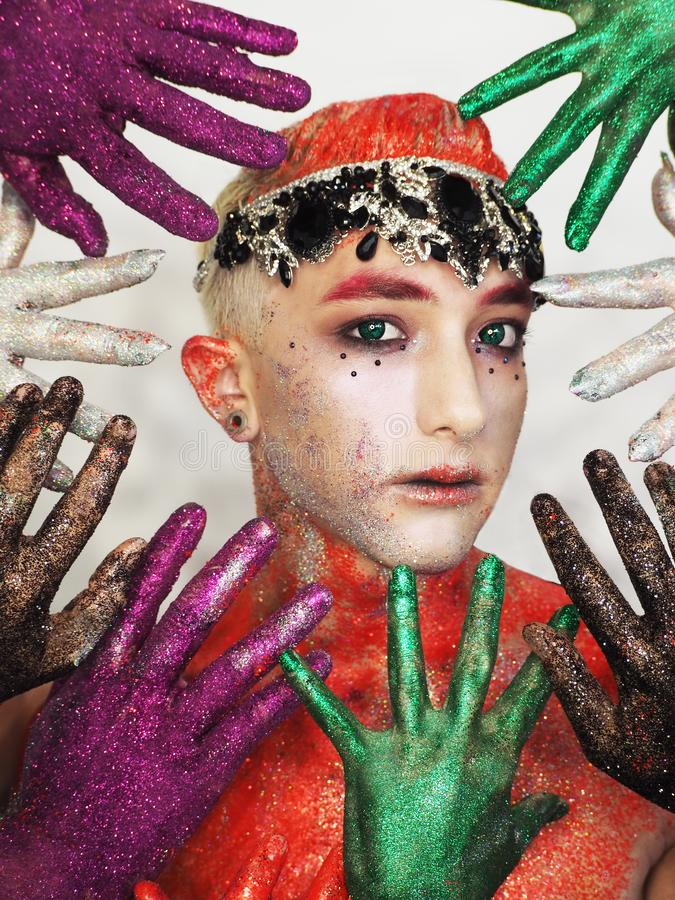 Man model at the art make- up with green eyes hiding from  the colorful hands. The Man model at the art make- up with green eyes hiding from  the colorful hands royalty free stock photo