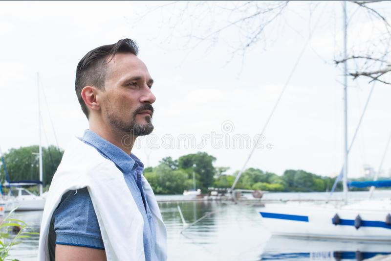 Man with model cut hair and bearded goatee. Portrait of young man with yacht. Man profile on the river bank. royalty free stock image