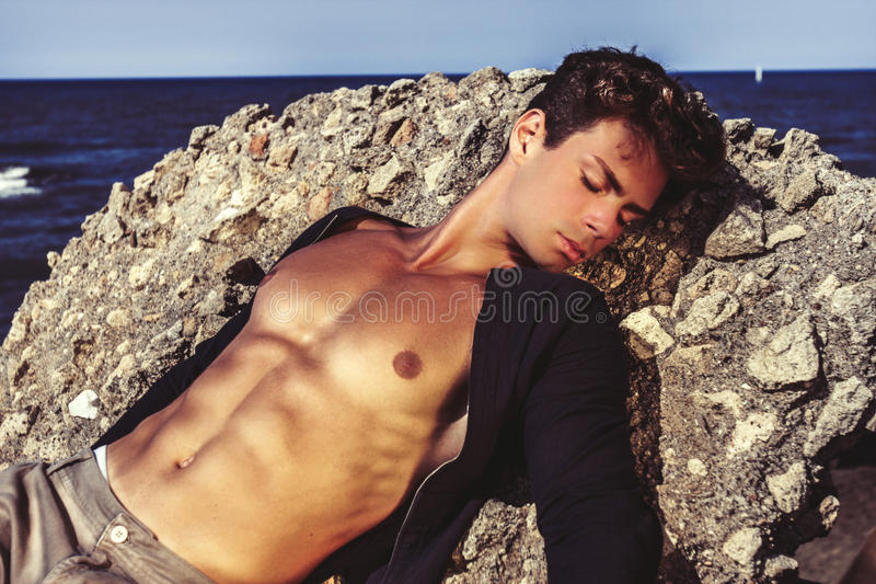 Man model. Summer seduction. A young boy is lying on a rock by the sea. Open shirt showing a lean and toned. Stylish hair. Concept of male seduction stock photo