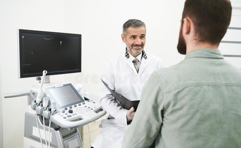Man in modern clinic on consultation with doctor. Man sitting in medical cabinet, with sonography eqipment in clinic. Cheerful, mature doctor consulting and stock photos