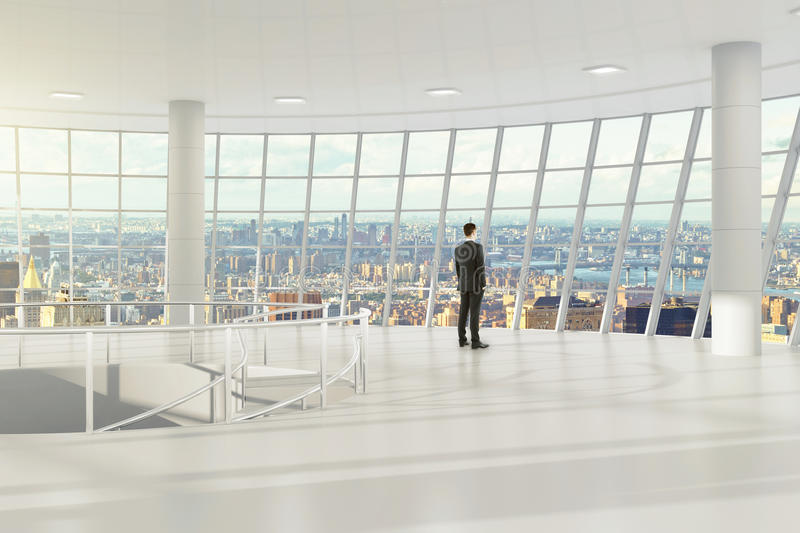 Man in modern light empty office with city view royalty free stock image