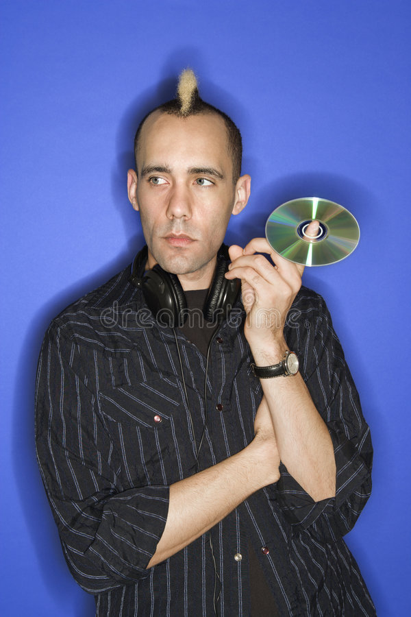 Man with mohawk holding cd. stock photography