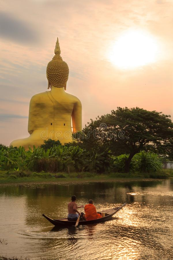 A man and monk riding on the rowing boat in the morning to Big Golden Buddha Image at Wat Muang stock images