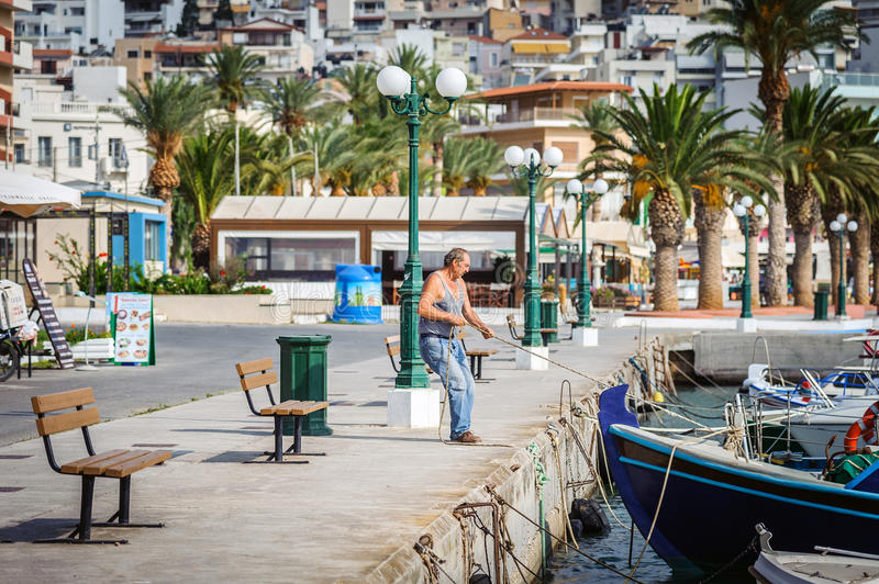 Man mooring his boat near pier of Sitia town on Crete island stock images